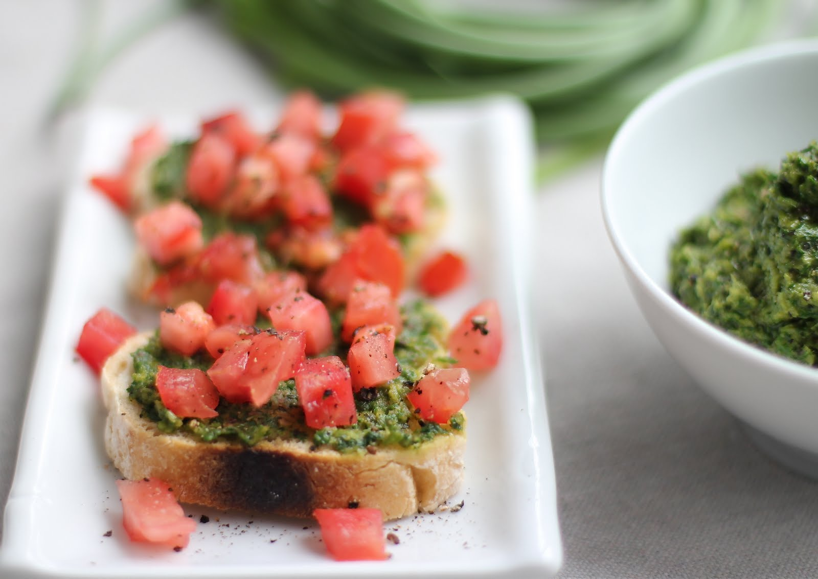 Toasted Gluten-Free Baguette Slices Topped with Swiss Chard Garlic Scape Pesto and Fresh Tomatoes